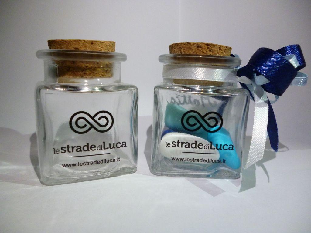 Vasetto in vetro con logo, bigliettino bianco con logo, nastro in raso (colore a scelta). Donazione 3€.